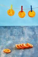 plakjes gedroogde sinaasappels of mandarijnen worden aan de waslijn gehangen foto