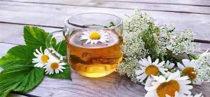 kamille aromatische thee in een glazen beker op een houten ondergrond. foto