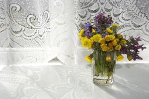 een boeket wilde bloemen in een vaas op tafel in de vroege ochtend foto