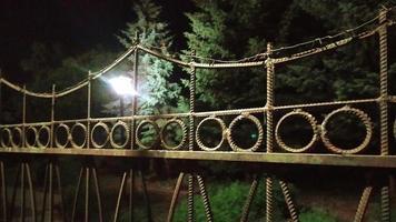 metalen hek 's nachts. kunstmatige lichtstralen dringen door foto