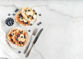 bovenaanzicht van vers gemaakte wafels met bosbessen, banaan en yoghurt foto