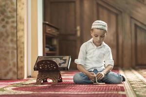 ramadan kareem, mooie jongen moslim bidt in moskee foto