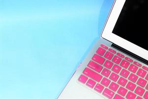 notitieboekje met roze toetsenbord. blauwe achtergrond foto