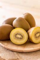 verse gouden kiwi in houten plaat foto