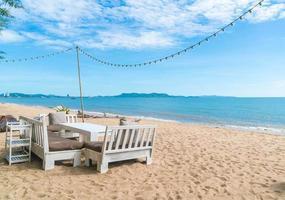 witte stoelen en tafel op het strand met uitzicht op de blauwe oceaan en de heldere lucht foto