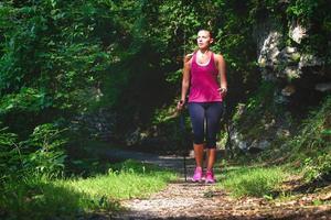 nordic-walking. een jonge vrouw op een wandeling in het bos foto