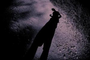 langwerpige schaduw van een man op grind foto