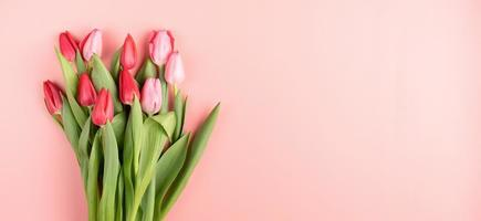 rode en roze tulpen op roze effen achtergrond bovenaanzicht plat lag foto