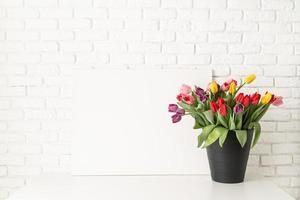 bespotten met frame en emmer tulpen op witte bakstenen muurachtergrond foto