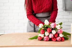 vrouwelijke bloemist die een boeket verse kleurrijke tulpen maakt foto