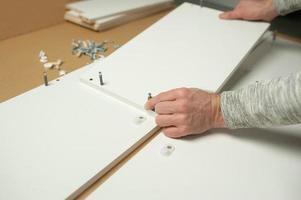 meester man installeer het monteren van meubels doe het zelf. reparaties aan huis foto