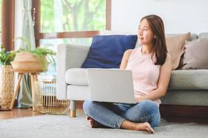 Aziatische vrouw die lacht terwijl ze thuis een laptop-notebook gebruikt foto