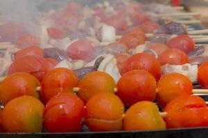 kippenharten met tomaat en ui koken op hete grill foto
