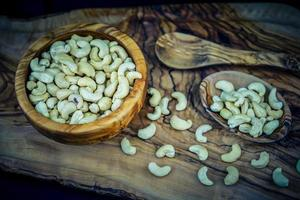 een stapel cashewnoten op olijfhout foto
