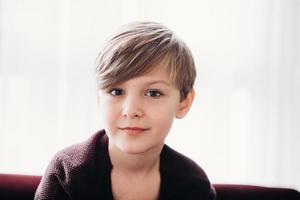 een schattige jongen die tegen het raam zit, soft focus foto