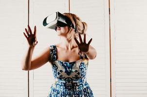 mooie vrouw die een vr-bril draagt en haar handen in de lucht wijst foto
