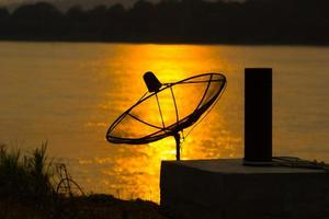 satellietschotel op de bezinning op de rivier in zonsondergangachtergrond foto