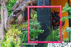 rood frame opgehangen aan boom in weelderige tuinomgeving foto