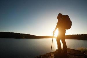 silhouet van wandelaar man met rugzak in zonsondergang landschap berg. foto