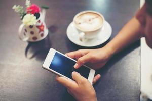 close-up van vrouw handen sms'en met haar mobiel bij coffeeshop. foto