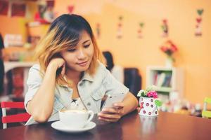 close-up van vrouw sms'en met haar mobiel in de coffeeshop. foto