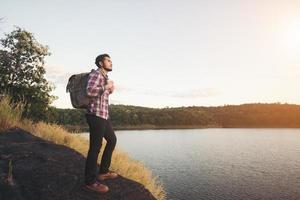 hipster wandelaar man die op de rots staat en geniet van de zonsondergang boven het meer. foto