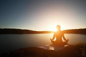 silhouet van gezonde vrouw oefent yoga meer tijdens zonsondergang. foto