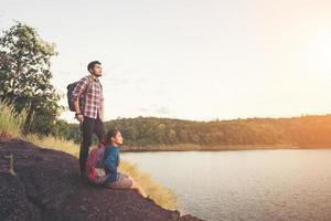 paar rust op de top van de berg onder uitzicht op het meer tijdens zonsondergang. foto