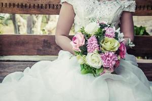 mooie verschillende kleuren in de handen van de bruid in een witte jurk foto
