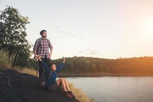 rust op de top van de berg onder uitzicht op het meer tijdens zonsondergang. foto