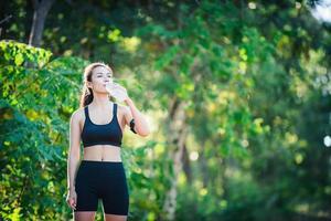 jonge vrouw die een pauze neemt tijdens het hardlopen. drinkwater uit de fles. foto