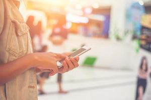 jonge vrouw hand met typende smartphone om te chatten in het winkelcentrum. foto
