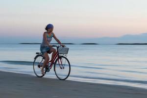 jonge vrouw tijdens een fietstocht op het strand vroeg in de ochtend foto