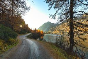 geïsoleerde bergweg in de buurt van het meer in de herfst bij zonsondergang foto