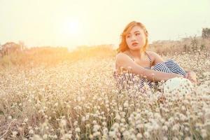 trieste vrouw zitten in bloemenveld en eenzaamheid foto