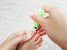 close-up aziatische moeder die de vingernagels van baby's voet knipt foto