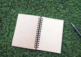 kraftpapier spiraal notebook met pen op het kunstgras foto