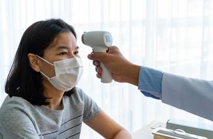 arts die digitale thermometer gebruikt om de temperatuur van de patiënt te meten foto