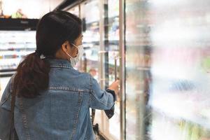jonge vrouw die een masker draagt tijdens het winkelen in de supermarkt foto