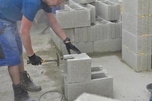 de metselaar metselwerk een muur van betonblokken op het huis foto