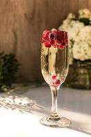 Mousserende wijn in glas met rode aalbessen foto