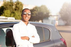 gelukkige afrikaanse amerikaan naast een auto in de zomer foto