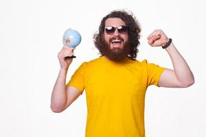 bebaarde man met zonnebril op houdt een wereldbol opgewonden foto