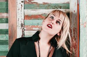 een mooi blond meisje in zwarte jurk lacht speels foto
