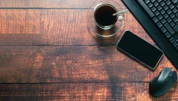 koffiemok, smartphone, toetsenbord, muis aan de balie. foto