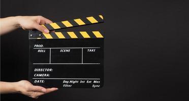 hand houdt gele en zwarte Filmklapper op zwarte achtergrond. foto