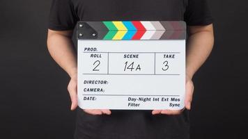 een man houdt een Filmklapper vast met een nummer op een zwarte achtergrond. foto