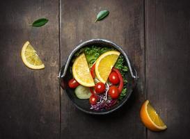 verse groentesalade met sinaasappel op de pan over houten achtergrond foto