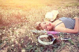 mooie sexy jonge vrouw die een hoofdtelefoon in het bloemenveld nadert foto