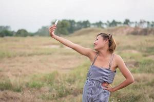 jonge vrouw staande met behulp van haar smartphone selfie in het grasveld. foto